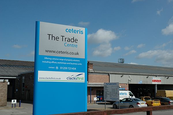 The Trade Centre entrance sign with the brick Industrial Trade Units building in the background