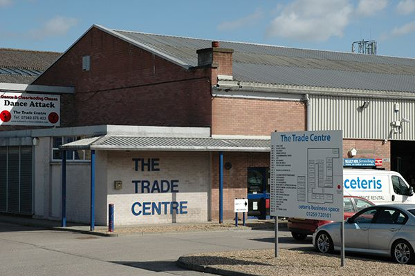 The Trade Centre tenant map sign and the white and red brick Industrial Trade Unit building behind it.