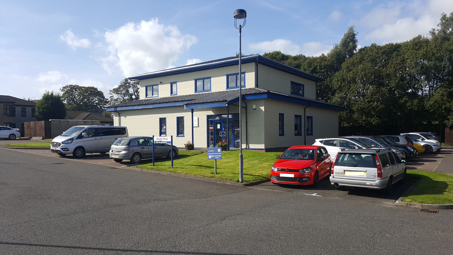 Bowden House from the outside, showing its tenant parking and bright exterior