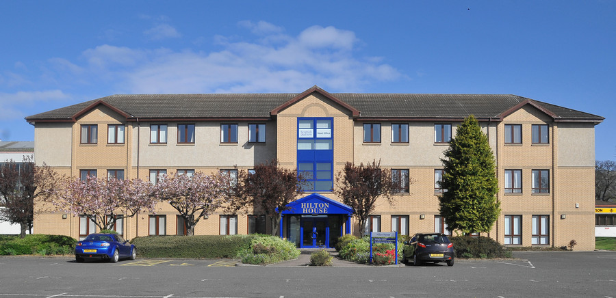 a front view of the Ceteris Hilton House offices in Alloa, made of light brick with a blue entrance way and ample private parking in front