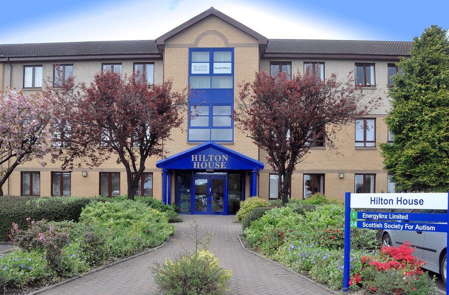 a front on view of the leafy walkway leading to the striking blue entrance of the Hilton House offices in Alloa