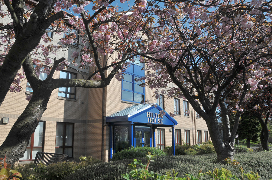 a side angled view of the leafy walkway leading to the striking blue entrance of the Hilton House offices in Alloa