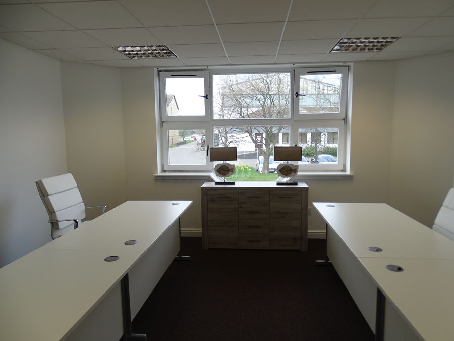 A contemporary office space with white chairs and desks and lots of natural light entering from a large window