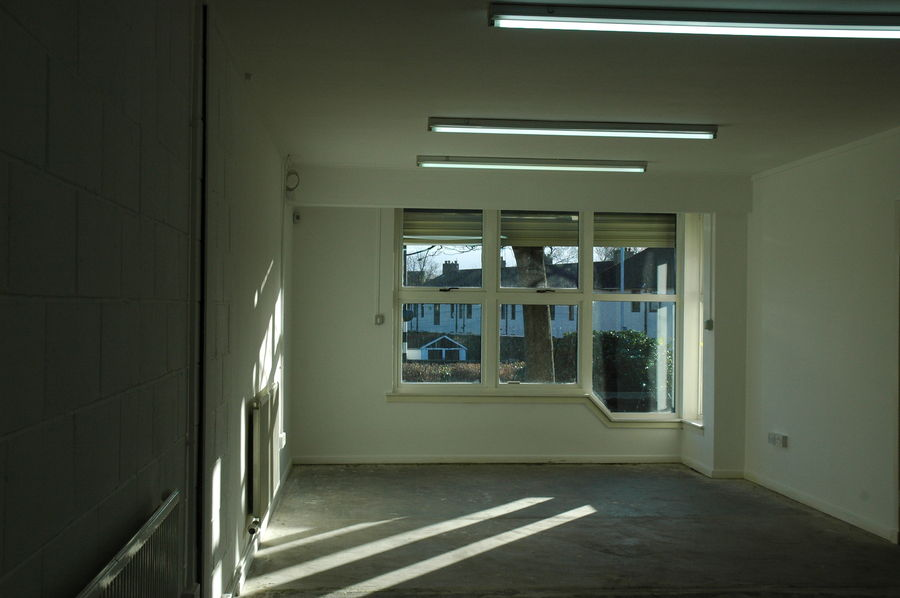 Inside one of the office areas of a Millar Court Business Industrial Unit in Alloa Business Park - with neutral colour walls and natural light from a corner window.